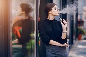 Young female smoking an e-cigarette.