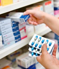 Pharmacist stocking shelves in a hospital pharmacy.