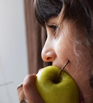 Little girl eating an apple.